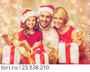 Купить «smiling family holding gift boxes and sparkles», фото № 23538210, снято 26 октября 2013 г. (c) Syda Productions / Фотобанк Лори