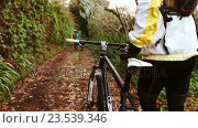 Купить «Mountain biking couple walking on forest trail with bike», видеоролик № 23539346, снято 20 июля 2019 г. (c) Wavebreak Media / Фотобанк Лори