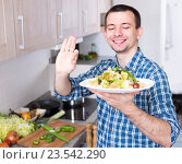 Купить «Молодой мужчина в клетчатой рубашке держит в руке тарелку с салатом и показывает жест ОК», фото № 23542290, снято 29 марта 2016 г. (c) Татьяна Яцевич / Фотобанк Лори