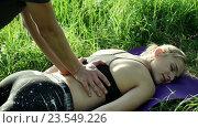 Тайский массаж. Девушка лежит на траве. Стоковое видео, видеограф ActionStore / Фотобанк Лори