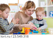 Купить «woman teaches kids handcraft at kindergarten or playschool», фото № 23549318, снято 23 февраля 2016 г. (c) Оксана Кузьмина / Фотобанк Лори