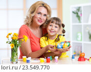 Купить «Mother and child girl showing painted Easter eggs at home interior», фото № 23549770, снято 6 августа 2015 г. (c) Оксана Кузьмина / Фотобанк Лори