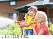 Купить «Little gardener girl with mother watering on lawn near house», фото № 23549822, снято 3 сентября 2015 г. (c) Оксана Кузьмина / Фотобанк Лори