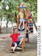 Купить «Kids sliding down together on playground's construction», фото № 23558054, снято 20 августа 2018 г. (c) Яков Филимонов / Фотобанк Лори