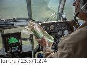 Пилот вертолёта ми-8 смотрит на карту (2016 год). Редакционное фото, фотограф Илья Ордовский-Танаевский / Фотобанк Лори