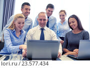 smiling business people with laptop in office, фото № 23577434, снято 25 октября 2014 г. (c) Syda Productions / Фотобанк Лори