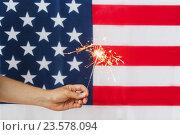 Купить «close up of hand with sparkler over american flag», фото № 23578094, снято 30 июня 2016 г. (c) Syda Productions / Фотобанк Лори