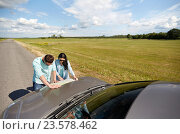 Купить «happy man and woman with road map on car hood», фото № 23578462, снято 12 июня 2016 г. (c) Syda Productions / Фотобанк Лори
