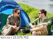 Купить «happy couple drinking beer at campsite tent», фото № 23579702, снято 27 мая 2016 г. (c) Syda Productions / Фотобанк Лори