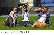 Купить «Трое студентов сидят на лужайке возле университета и общаются», видеоролик № 23579818, снято 13 сентября 2016 г. (c) Виктор Аллин / Фотобанк Лори