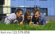 Купить «Трое студентов лежат на лужайке с телефонами», видеоролик № 23579858, снято 13 сентября 2016 г. (c) Виктор Аллин / Фотобанк Лори