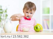 Купить «happy kid girl eating food itself with spoon», фото № 23582382, снято 13 мая 2015 г. (c) Оксана Кузьмина / Фотобанк Лори