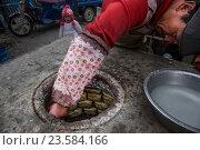 Купить «Мужчина выпекает самсу в тандыре на центральной улице в центре города Ташкурган Таджикского автономного уезда в Синьцзяне Китая», фото № 23584166, снято 20 марта 2016 г. (c) Николай Винокуров / Фотобанк Лори