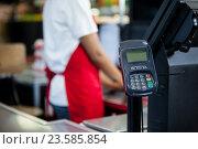 Купить «Credit card terminal at cash counter», фото № 23585854, снято 9 мая 2016 г. (c) Wavebreak Media / Фотобанк Лори