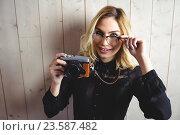 Купить «Beautiful woman posing with camera and spectacle against texture background», фото № 23587482, снято 15 февраля 2016 г. (c) Wavebreak Media / Фотобанк Лори