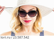 Купить «Beautiful woman posing with hat against white background», фото № 23587542, снято 15 февраля 2016 г. (c) Wavebreak Media / Фотобанк Лори