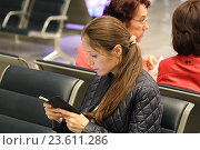 Купить «Девушка в зале ожидания в аэропорте смотрит на смартфон», фото № 23611286, снято 11 сентября 2016 г. (c) Алексей Сварцов / Фотобанк Лори
