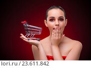 Купить «Woman with shopping cart against red background», фото № 23611842, снято 18 июля 2016 г. (c) Elnur / Фотобанк Лори