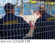 Купить «Два контролера сидят на скамейке за защитным периметром», эксклюзивное фото № 23629138, снято 15 июня 2016 г. (c) Вячеслав Палес / Фотобанк Лори