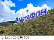 """Купить «Логотип сотового оператора """"Мегафон"""" на склоне горы Мархотского хребта в городе курорте Геленджик, Краснодарский край», фото № 23636606, снято 7 июля 2016 г. (c) Иван Карпов / Фотобанк Лори"""