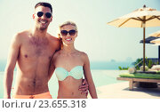 Купить «happy couple in swimwear hugging over hotel resort», фото № 23655318, снято 11 августа 2015 г. (c) Syda Productions / Фотобанк Лори