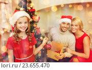 Купить «smiling family decorating christmas tree», фото № 23655470, снято 26 октября 2013 г. (c) Syda Productions / Фотобанк Лори