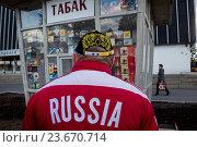 Купить «Мужчина в одежде с российской символикой смотрит на витрину табачного киоска с советскими пачками сигарет на центральной аллее ВДНХ в городе Москве, Россия», фото № 23670714, снято 25 апреля 2015 г. (c) Николай Винокуров / Фотобанк Лори
