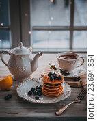 Купить «Оладьи с ягодами и чай на столе», фото № 23694854, снято 7 января 2016 г. (c) Вероника Галкина / Фотобанк Лори
