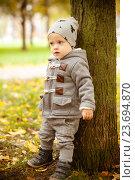 Купить «Маленький мальчик стоит у дерева в осеннем парке», фото № 23694870, снято 30 сентября 2016 г. (c) Вероника Галкина / Фотобанк Лори