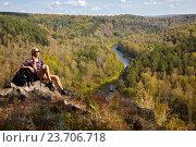Купить «Young blonde woman tourist with backpack sitting on a cliff on background of siberian autumn landscape with the river Berd», фото № 23706718, снято 8 сентября 2016 г. (c) Serg Zastavkin / Фотобанк Лори