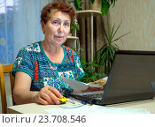 Купить «Пожилая женщина пользуется компьютером в повседневной жизни», эксклюзивное фото № 23708546, снято 19 июня 2016 г. (c) Вячеслав Палес / Фотобанк Лори