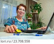 Купить «Пожилая улыбающаяся женщина сидит за столом перед ноутбуком», фото № 23708558, снято 19 июня 2016 г. (c) Вячеслав Палес / Фотобанк Лори