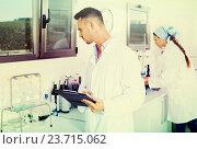 Купить «Man checking quality of wine in chemical laboratory», фото № 23715062, снято 17 октября 2019 г. (c) Яков Филимонов / Фотобанк Лори