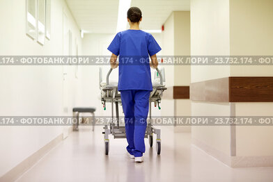 nurse carrying hospital gurney to emergency room
