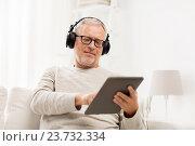 Купить «senior man with tablet pc and headphones at home», фото № 23732334, снято 7 июля 2016 г. (c) Syda Productions / Фотобанк Лори