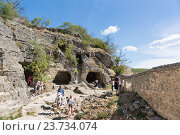 Купить «Туристы осматривают и фотографируют скалы пещерного города Чуфут-Кале. Бахчисарай, Крым», фото № 23734074, снято 13 сентября 2016 г. (c) Наталья Гармашева / Фотобанк Лори