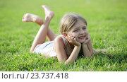 glad small girl lying on green grass in park. Стоковое видео, видеограф Яков Филимонов / Фотобанк Лори