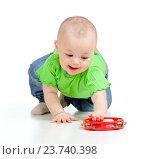 Купить «Baby girl playing with musical toy. Isolated on white background», фото № 23740398, снято 24 февраля 2012 г. (c) Оксана Кузьмина / Фотобанк Лори