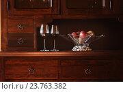 Два бокала красного вина и яблоки в стеклянной вазе с серебряным основанием на деревянном буфете. Стоковое фото, фотограф Закирова Наталья / Фотобанк Лори