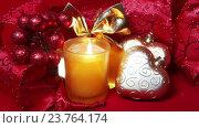 Купить «Новогодние украшения и горящая свеча на красном фоне», видеоролик № 23764174, снято 12 октября 2009 г. (c) Куликов Константин / Фотобанк Лори