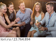 Man popping a champagne bottle while friends watching him. Стоковое фото, агентство Wavebreak Media / Фотобанк Лори