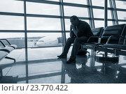 Купить «Грустный человек в ожидании задержанного рейса в аэропорту», фото № 23770422, снято 5 октября 2016 г. (c) Антон Гвоздиков / Фотобанк Лори