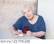 Купить «Единовременная выплата пенсионерам. Пожилая женщина с пенсионным удостоверением и пятью тысячами рублей», фото № 23774226, снято 2 февраля 2011 г. (c) Дудакова / Фотобанк Лори