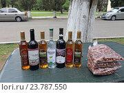 Купить «Бутылки абхазского вина, чачи, водки и пакеты орехов фундук на столе для продажи, Абхазия», эксклюзивное фото № 23787550, снято 20 июля 2016 г. (c) Алексей Гусев / Фотобанк Лори