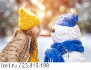 girl playing with a snowman. Стоковое фото, фотограф Константин Юганов / Фотобанк Лори
