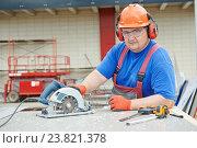 Купить «Worker builder cutting material», фото № 23821378, снято 24 мая 2013 г. (c) Дмитрий Калиновский / Фотобанк Лори