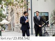 Купить «Two young businessmen with a bike in city centre», фото № 23858542, снято 4 апреля 2015 г. (c) Sergey Nivens / Фотобанк Лори