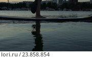 Женщина с веслом на доске плывет по реке на закате. Стоковое видео, видеограф Станислав Толстнев / Фотобанк Лори