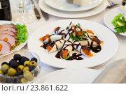 Блины с красной икрой на тарелке среди закусок на столе. Стоковое фото, фотограф Кекяляйнен Андрей / Фотобанк Лори