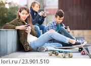 Купить «Three teenagers with smartphones», фото № 23901510, снято 23 октября 2018 г. (c) Яков Филимонов / Фотобанк Лори